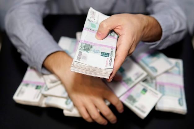 Męskie ręce sięgają po zwitek pieniędzy. milion rubli rosyjskich na czarnym stole. pojęcie bogactwa, sukcesu, chciwości i korupcji, żądzy pieniędzy