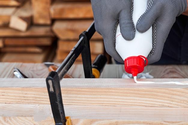 Męskie ręce stolarza przy użyciu kleju do drewna i drewna na drewnianym stole do ręcznie robionych mebli.