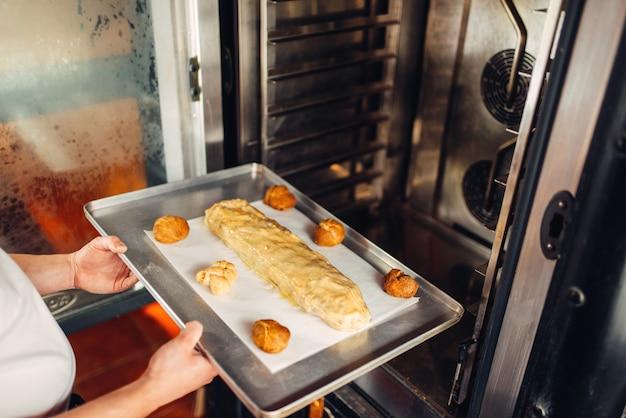 Męskie ręce szefa kuchni kładzie strudel jabłkowy na blasze do pieczenia w piekarniku. słodka piekarnia, przygotowanie deserów