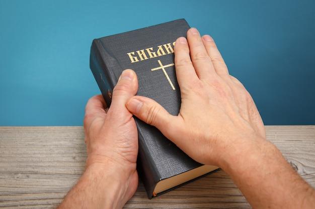 Męskie ręce trzymają biblię opartą na drewnianym stole. tytuł książki tłumaczenie holly bible
