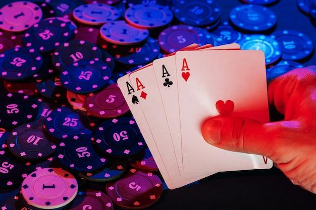 Męskie ręce trzymają karty, na tle zestaw asów