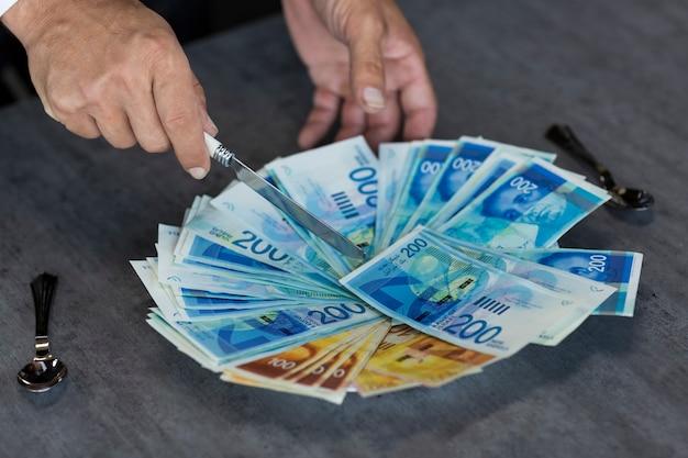 Męskie ręce trzymają nóż i odcinają kawałek nowej waluty izraelskich szekli. bankowość lokalna, koncepcja lunchu biznesowego. pomysł na wizualizację podatków, dewaluacji i odsetek.