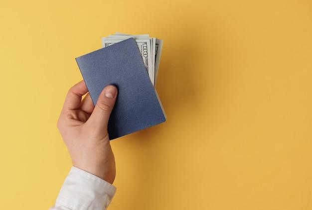 Męskie ręce trzymają paszport z pieniędzmi na żółtym tle. podróże, wakacje.widok z góry