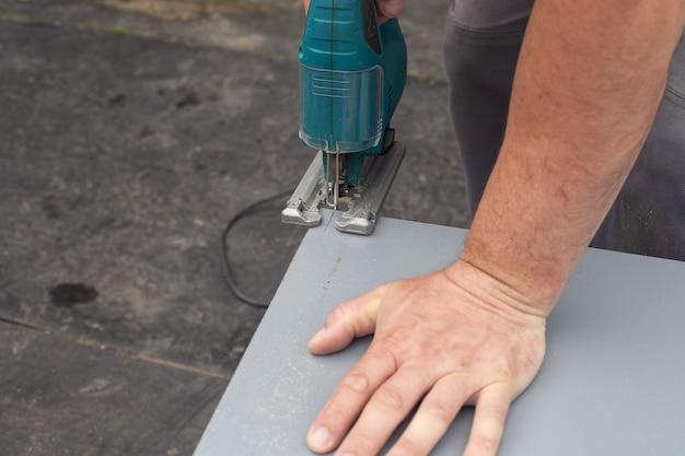 Męskie ręce trzymają piłę. domowe rzeźbienie małego kawałka sklejki za pomocą elektrycznej wyrzynarki