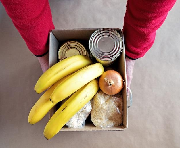 Męskie ręce trzymają pudełko na datki żywności. koncepcja darowizny i dostarczania żywności.