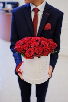Męskie ręce trzymają wiadro czerwonych róż w wiadrze