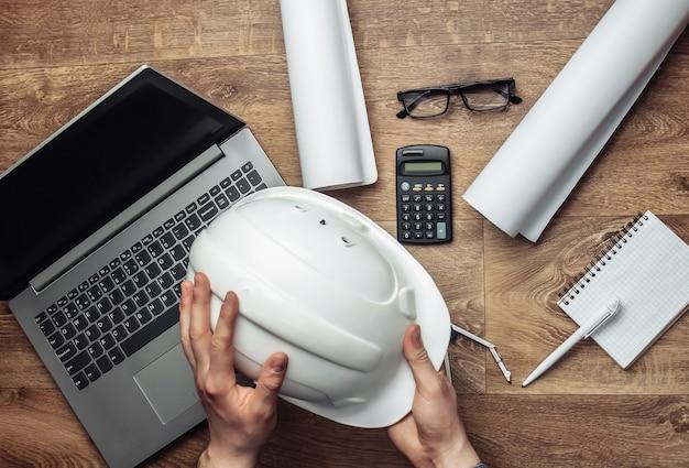 Męskie ręce trzymając hełm konstrukcyjny w miejscu pracy.