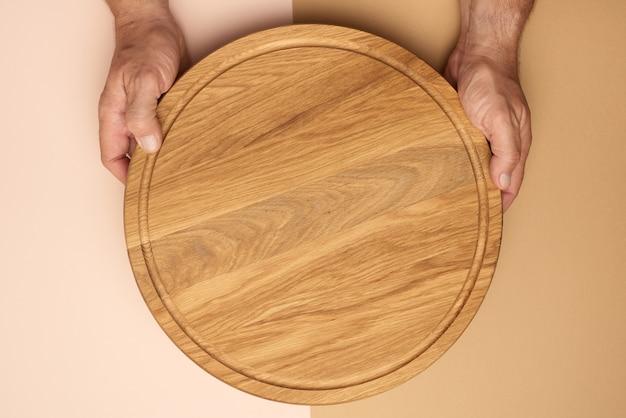 Męskie ręce trzymając okrągły pusty deska do pizzy