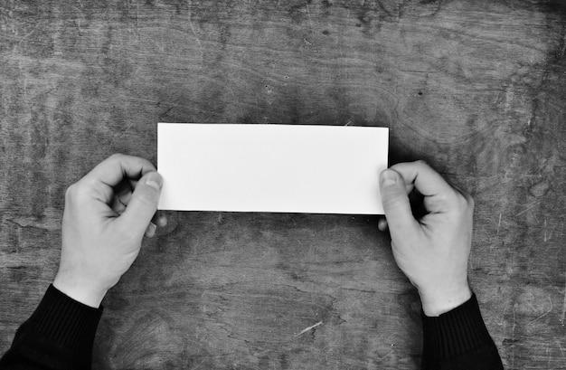 Męskie ręce trzymające białą pustą kartkę papieru na tle drewnianego stołu tekstury
