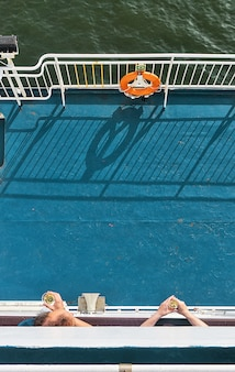 Męskie ręce trzymające kieliszki wina na tle niebieskiego pokładu statku