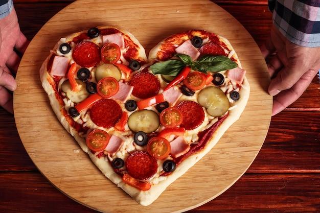 Męskie ręce trzymające kształty serca pizza koncepcja prezentu niespodzianka walentynki