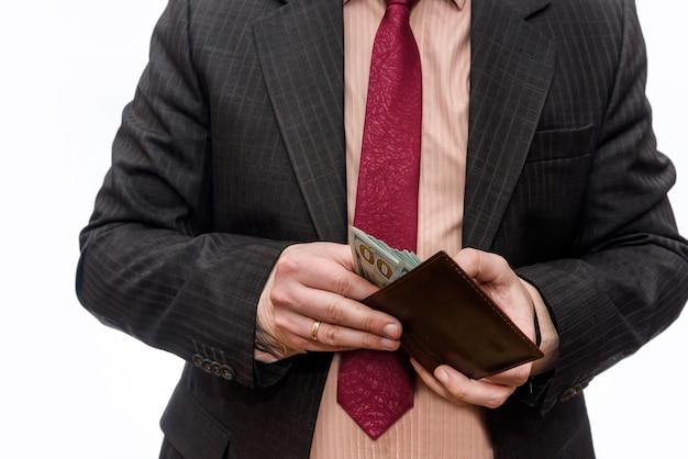 Męskie ręce trzymające portfel pełen banknotów dolarowych z bliska