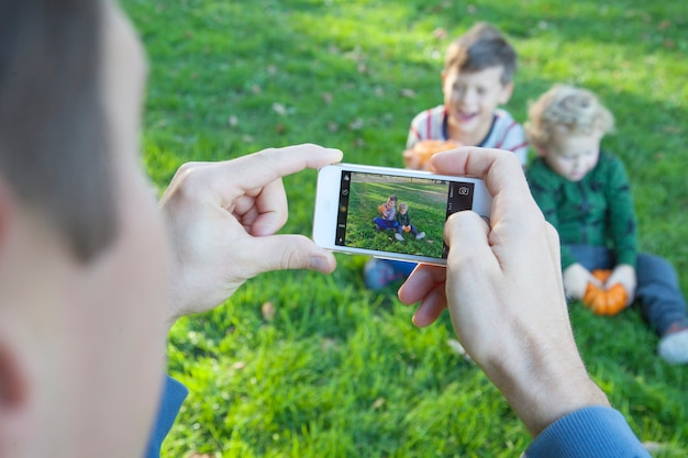 Męskie ręce trzymające smartfon i robienie zdjęć szczęśliwych dzieci. ojciec robi zdjęcia swoim dzieciom przez telefon w przyrodzie. zbliżenie