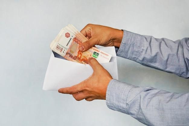 Męskie ręce uważają ruble za wartość nominalną w wysokości 5000 rubli. ręka z rublami w kopercie na półkach w supermarkecie
