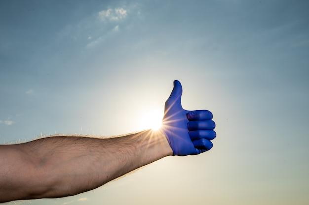 Męskie ręce w niebieskich rękawiczkach medycznych. covid-19. koronawirus. scena pochmurnego nieba.