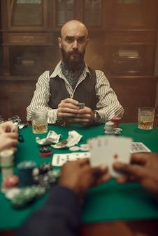 Męskie ręce z kartami, pokerem, grami losowymi