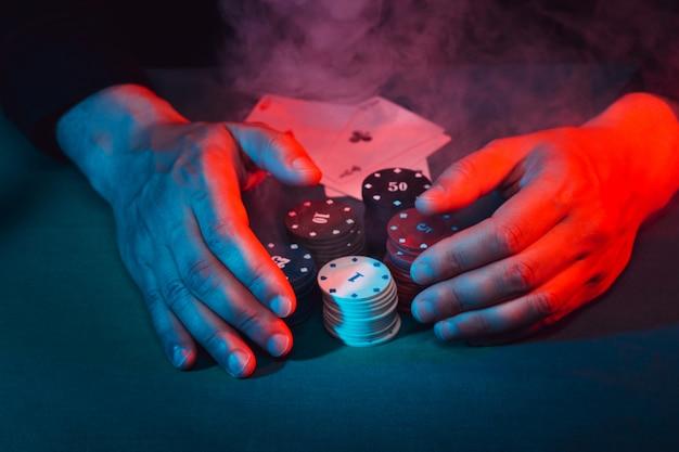 Męskie ręce zabierają żetony do gry w zakład postawione