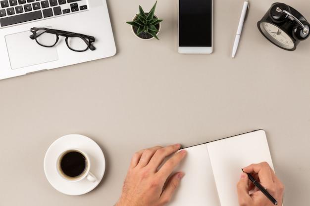 Męskie ręki pisze w pustej notepad stronie na nowożytnym biurowym biurku przed laptopem