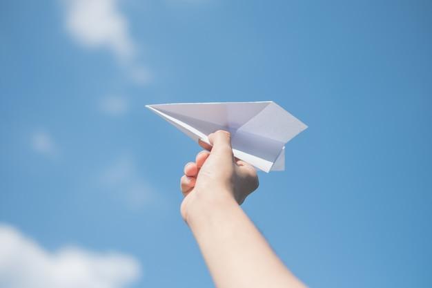 Męskie ręki trzyma białą papierową rakietę z jaskrawym błękitnym tłem.