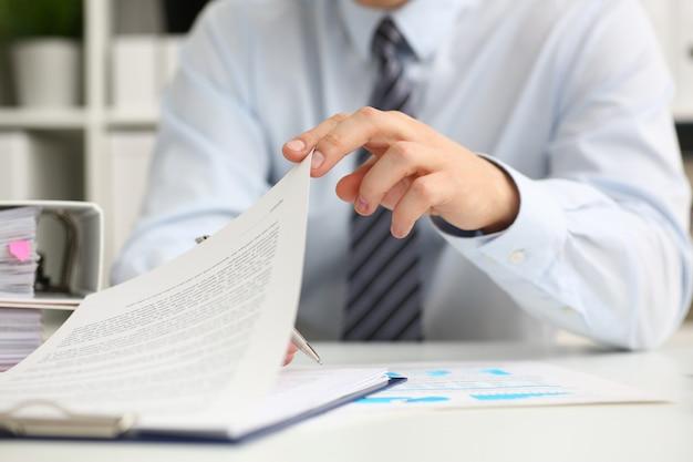 Męskie ręki trzymają dokumenty z pieniężnym