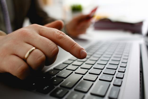 Męskie ręki trzymają kredytowej karty prasy guziki robi przeniesienia zbliżeniu. zabezpieczenie finansowe przed oszustwem przy wprowadzaniu numeru programu rabatowego klienta lub wypełnianiu osobistego hasła logowania do konta
