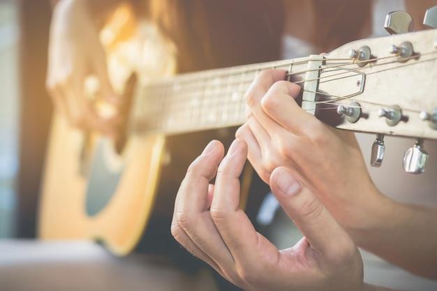 Męskie ręki uczą kobiety bawić się gitarę ten wizerunek jest zamazany i miękka ostrość.