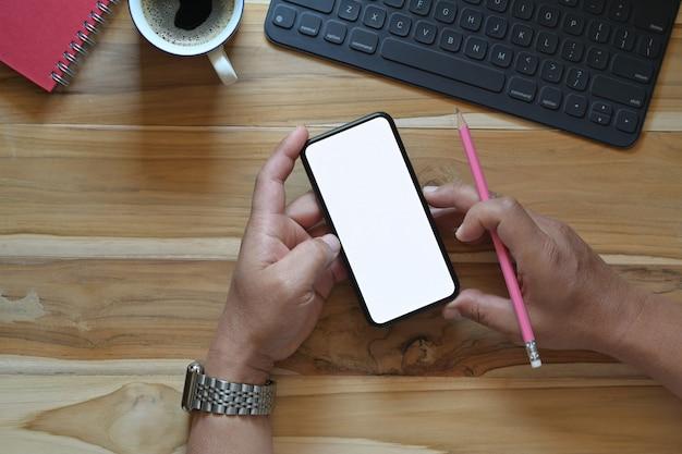 Męskie ręki używać smartphone pustego ekranu mockup przy biurowym biurkiem