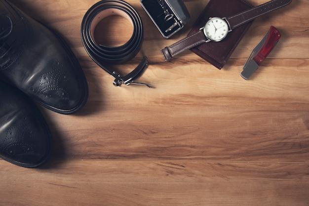 Męskie skórzane akcesoria na drewnianym stole.