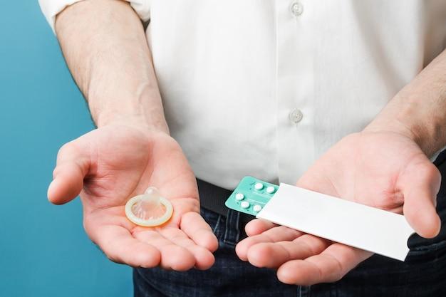 Męskie środki antykoncepcyjne. tabletki i prezerwatywa w rękach mężczyzn