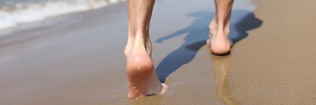 Męskie stopy chodzenia po piasku na plaży zbliżenie