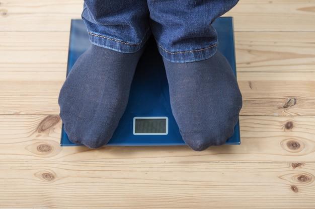 Męskie stopy na podłodze skalują się