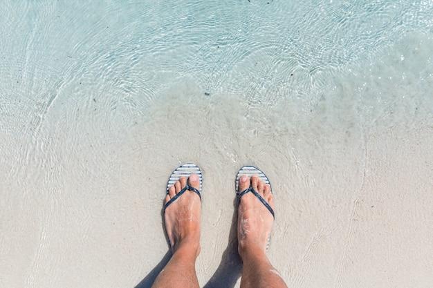 Męskie stopy na sobie klapki kobiece na plaży