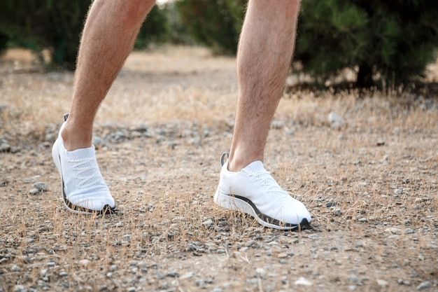 Męskie stopy w białych tenisówkach na nierównym terenie. biegi przełajowe z naciskiem na nogi biegacza.