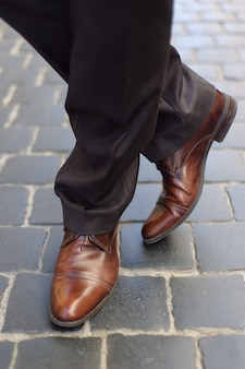 Męskie stopy w butach na chodniku