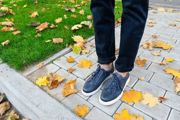 Męskie stopy w parku na chodniku