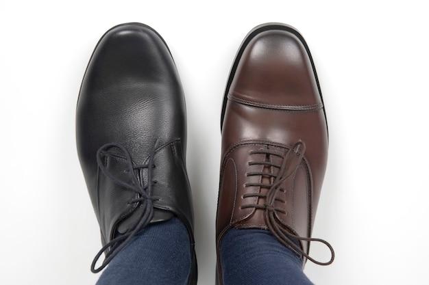 Męskie stopy w różnokolorowych klasycznych butach na białym tle