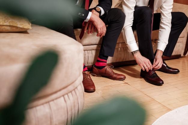 Męskie stopy w stylowych butach i jasnych skarpetach. elegancki mężczyzna ubiera buty. dwie męskie ręce wiążą sznurowadła. moda męska. moda ślubna.