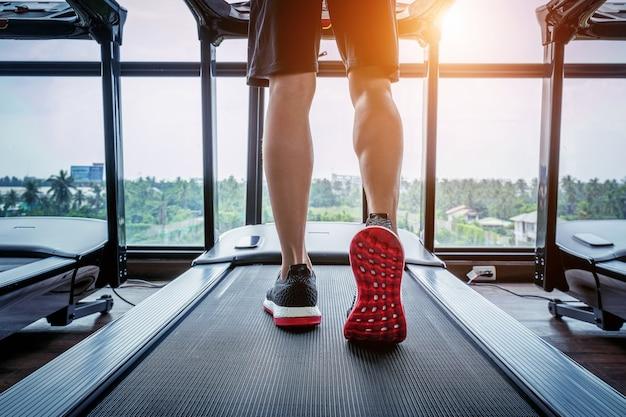 Męskie stopy w trampkach na bieżni na siłowni. koncepcja ćwiczeń.