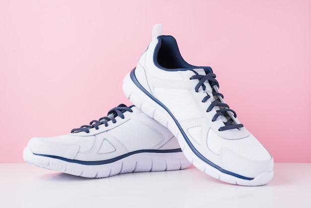 Męskie trampki do biegania na różowym tle. białe moda stylowe buty sportowe, z bliska