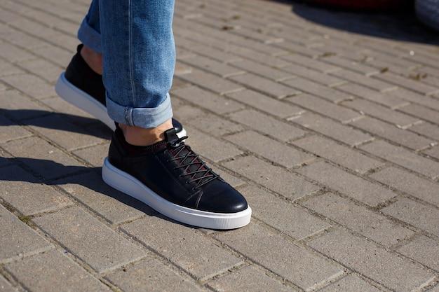 Męskie trampki lub buty z prawdziwej skóry na męskich nogach z bliska.