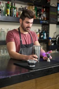 Męskiego barmanu sumujący składnik w potrząsaczu przy baru kontuarem