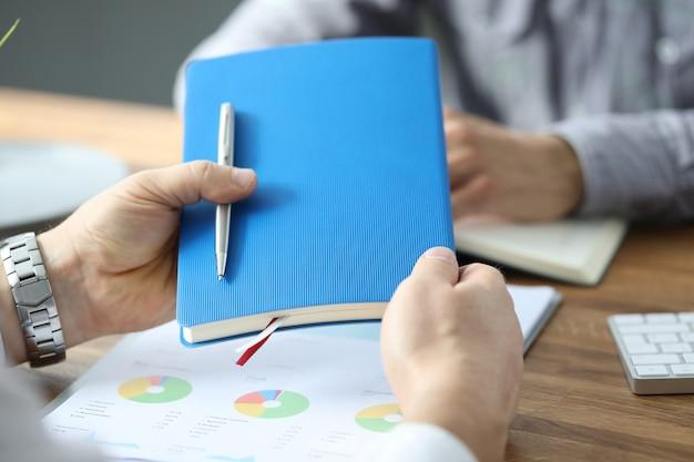 Męskiego biznesmen ręki chwyta błękitny dzienniczek z srebnym piórem przeciw biurowemu bacground. koncepcja pracy firmy