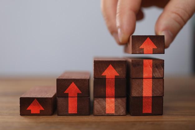 Męskiego biznesmen ręki chwyta brązu drewniany blok przeciw