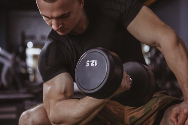 Męskiego bodybuilder podnośni dumbbells przy gym