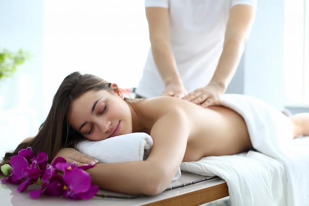Męskiego masażysty ręka robi kręgosłupa plecy masażowi młodej caucasian kobiety przeciw zdroju gabinetowemu tła portretowi. koncepcja odnowy biologicznej piękna
