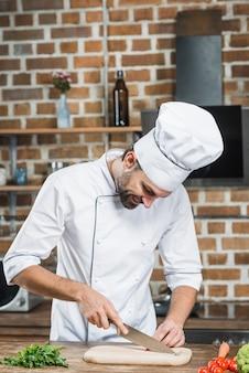 Męskiego szefa kuchni tnący czerwony chili na ciapanie desce