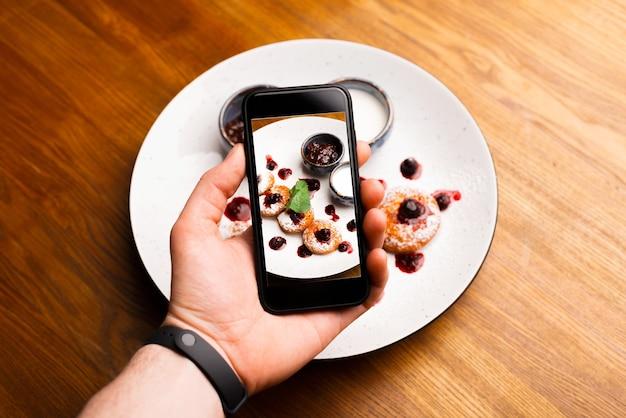 Męskiej dłoni fotografowanie porannego talerza z naleśnikami z klejnotem na drewnianym
