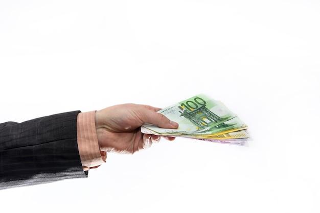 Męskiej dłoni, podając banknoty euro na białym tle