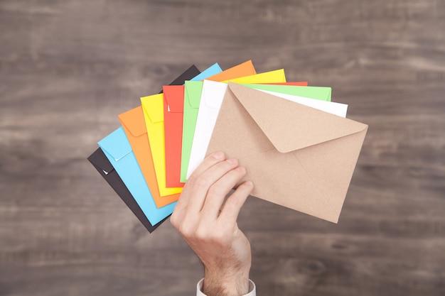 Męskiej dłoni pokazano kolorowe koperty pocztowe na drewnianym stole.