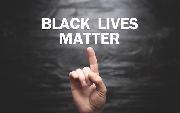 Męskiej dłoni pokazano tekst black lives matter na czarnym tle.